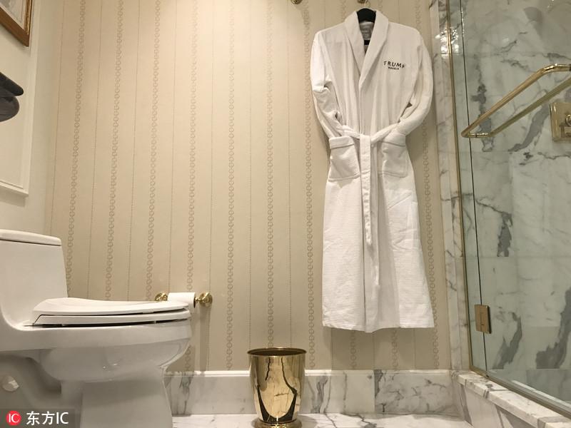 """当地时间2017年2月报道,特朗普一直坚持""""把制造业搬回美国""""的旗号,最终问鼎总统宝座。然而这句话尚未落到实处就遭""""打脸"""",当英媒《每日镜报》的记者,探访特朗普集团花2亿美元打造的一家五星级的特朗普国际酒店,却发现酒店房间内的设施,从电视机到毛巾几乎都是在外国制造。当地时间2017年1月30日,美国华盛顿,特朗普国际酒店内,浴衣为中国制造,而黄铜垃圾桶为英国制造。"""